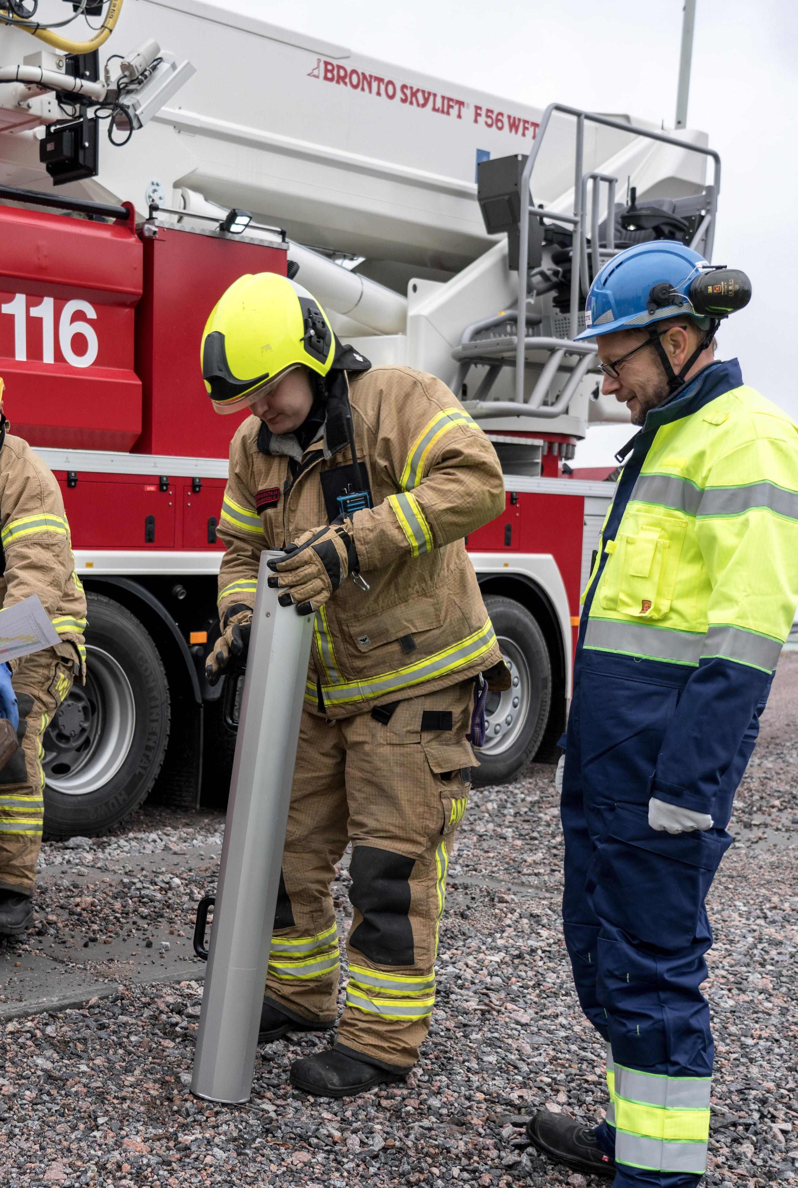 Fire fighter ensuring ground safety with Bronto loadman